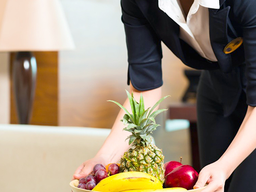 Asian Chinese hotel executive housekeeper placing fruit treatmen